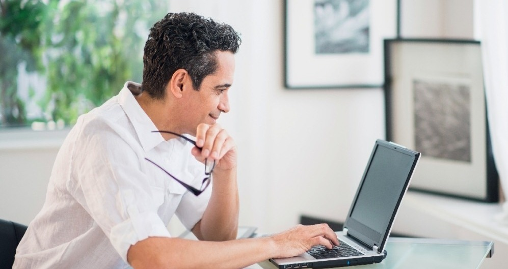 man smiling while browsing on a laptop