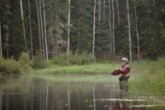 man fly fishing in a pond