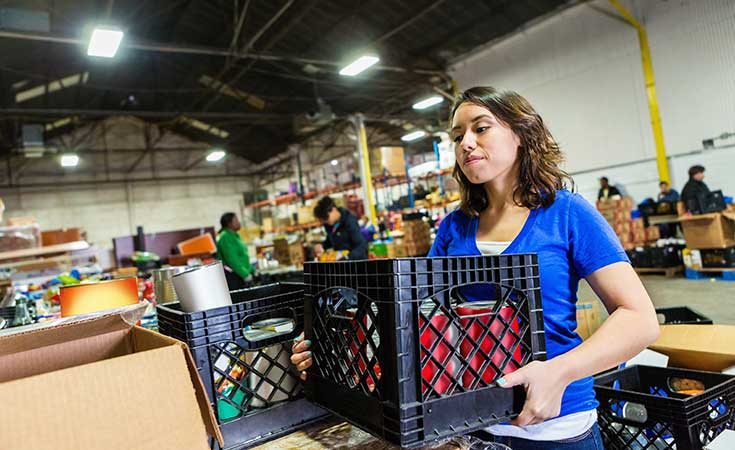 woman stacking crates full of items