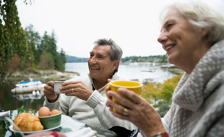 older couple smiling and drinking coffee outside