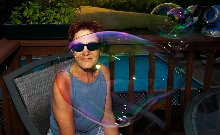 woman sitting outside with giant bubble floating across her face
