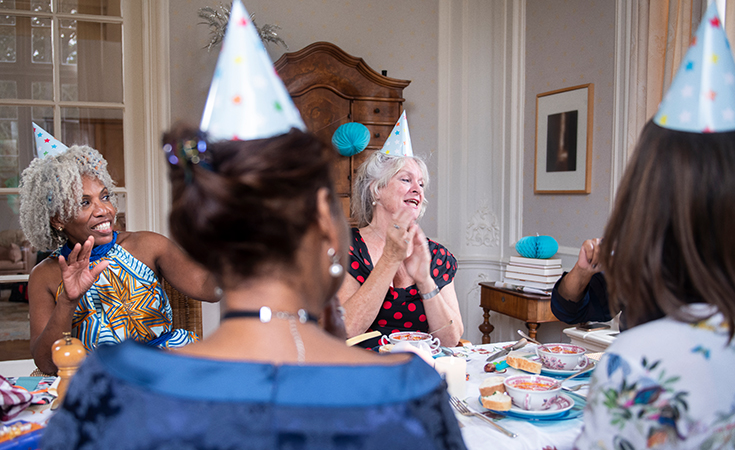 older women wearing party hats and singing and clapping