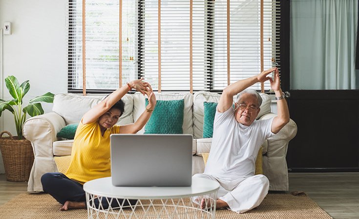older asian couple doing a virtual yoga class