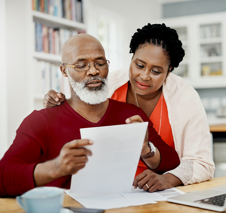 older black couple embracing and looking at a piece of paper together