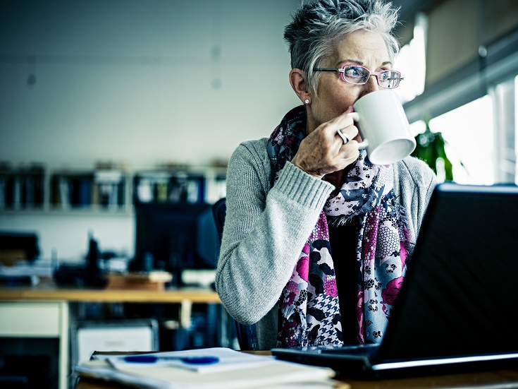 older woman drinking coffee while on her laptop