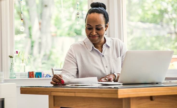 black business woman smiling while working at desk