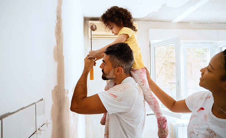father holding daugther on shoulders while painting a wall
