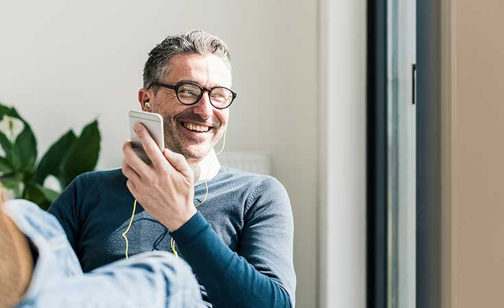 man smiling while listening to something on his phone
