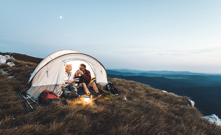 older couple sitting in a tent in the outdoors