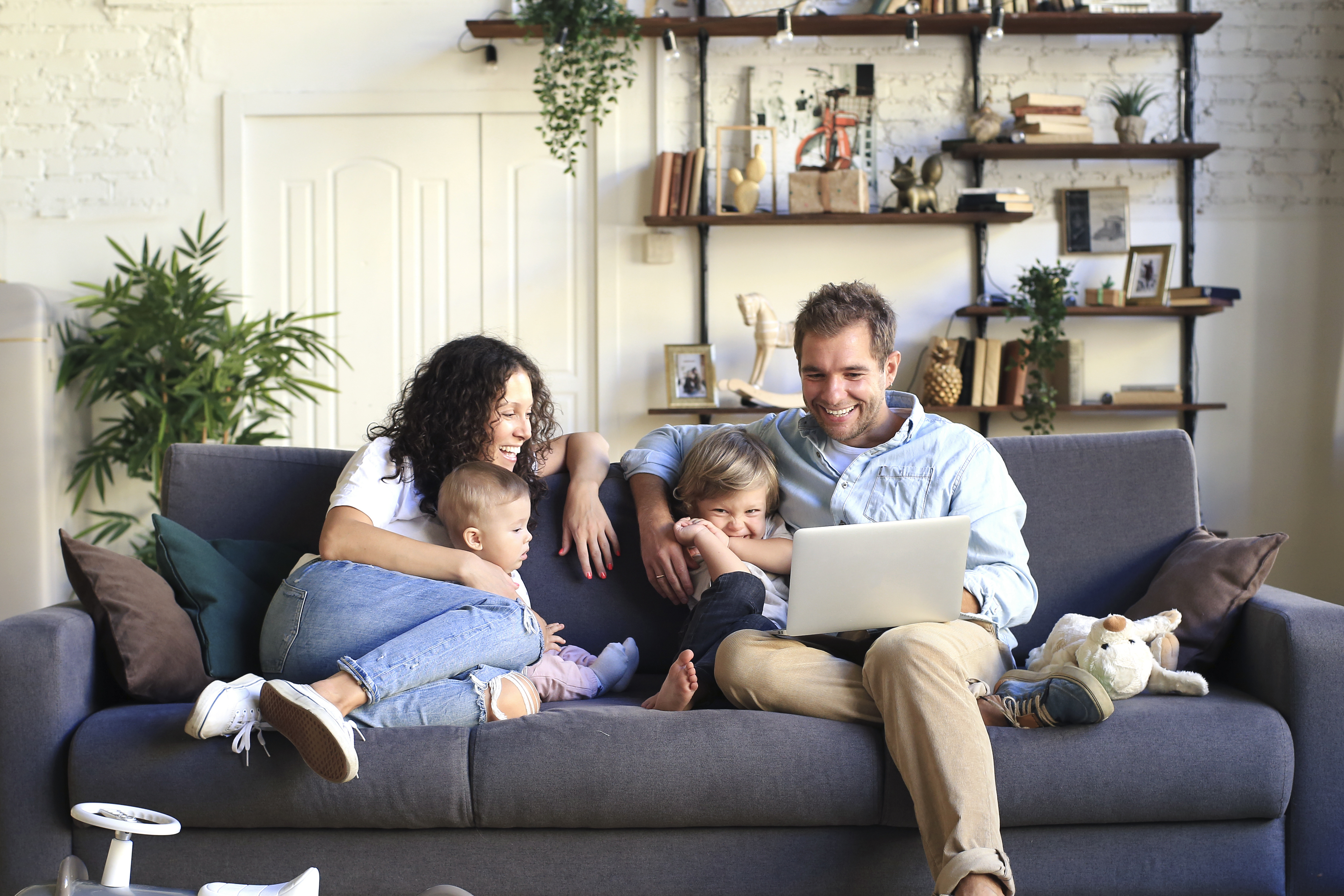 Family sitting on sofa looking at computer