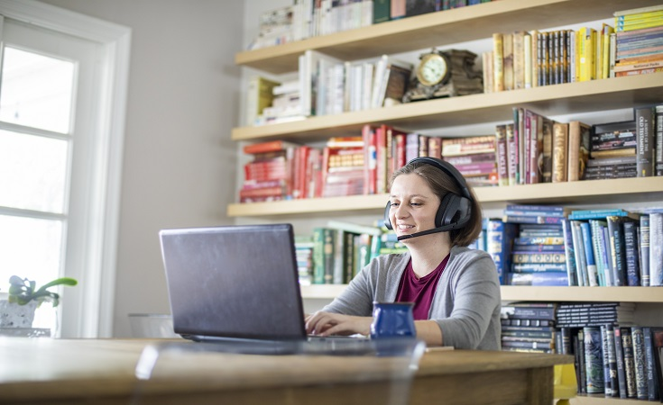 Woman sitting at a computer with headphones
